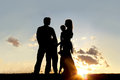 Silhouette of Happy Family and Dog Outside at Sunset Royalty Free Stock Photo