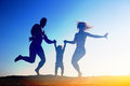 Silhouette of happy family jumping on the beach Royalty Free Stock Photography