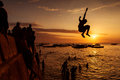 Silhouette of Happy Young boy jumping in water at sunset in Zanz Royalty Free Stock Photo