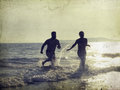 Silhouette of happy young teens playing on the beach at beautiful summer sunset Stock Photo