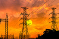 Silhouette high voltage electric pillars on sunset background