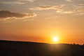 Silhouette of hill on sunset with sun and clouds Stock Photos