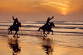 Silhouette of a horse and rider galloping on beach at sunset Royalty Free Stock Photo