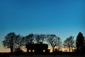 Silhouette house bare trees dark blue sky evening Stock Photo