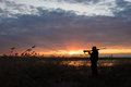 Silhouette of the hunter at sunset in spring duck hunt Royalty Free Stock Images