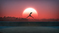 Silhouette of jumping ballet woman with skyline of skyscraper city in the background. Sunset with large sun. Royalty Free Stock Photo