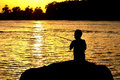 Silhouette of kid fishing Royalty Free Stock Photo