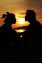 Silhouette kissing on the beach sunset Stock Photos