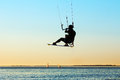 Silhouette of a kitesurfer flying above the water at sunset Royalty Free Stock Image