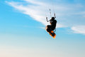 Silhouette of a kitesurfer flying in the blue sky Stock Images