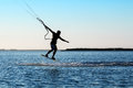 Silhouette of a kitesurfer jumping over the water Stock Photos