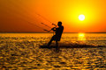 Silhouette of a kitesurfer sailing in the evening Stock Photos