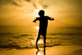 Silhouette of little boy jumping over the beach wave sunshine Royalty Free Stock Photo