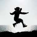 Silhouette of a little girl jumping on background the sea at sunset Stock Photography
