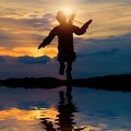 Silhouette of a little girl jumping on background the sea at sunset Royalty Free Stock Image
