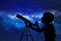 Silhouette of little girl looking through a telescope Royalty Free Stock Photo