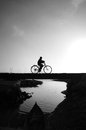 Silhouette of lonely young boy riding bicycle on small bridge cross the river at morning he ride bike leisure this make sad calm Royalty Free Stock Photos