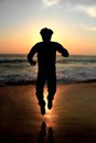 Silhouette male adult jumping at a beach Stock Images