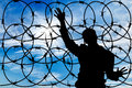 Silhouette male refugee and a barbed wire fence