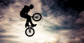 Silhouette of a man with bmx bike doing an jump color toned image Stock Image