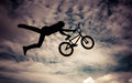 Silhouette of a man with bmx bike doing an jump color toned image Royalty Free Stock Photography