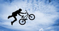 Silhouette of a man with bmx bike doing an jump color toned image Stock Photography