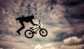 Silhouette of a man with bmx bike doing an jump color toned image Royalty Free Stock Image
