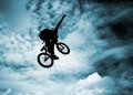 Silhouette of a man with bmx bike doing an jump color toned image Stock Photo