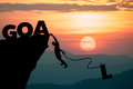 Silhouette man climbs into cliff to make word goal goal setting concept the Royalty Free Stock Image