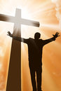 Silhouette of a man at the cross praising jesus with light beams Royalty Free Stock Images