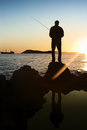 Silhouette man fishing shore sea sunset boat background Royalty Free Stock Photography