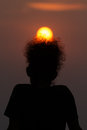 Silhouette of a man with golden sun rise on his afro hair style Stock Image