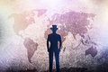 Silhouette of a man in hat standing in front of world map on grunge concrete wall Royalty Free Stock Photo