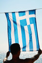 Silhouette of Man holding Greek flag. Man holding  flag of Greece in front of sea Royalty Free Stock Photo
