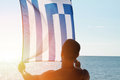 Silhouette of Man holding Greek flag. Man holding flag of Greece in front of sea. Sunset colors