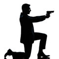 Silhouette man kneeling aiming gun Stock Images