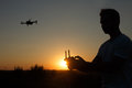 Silhouette of a man piloting drone in the air with a remote controller in his hands on sunset. Pilot takes aerial photos