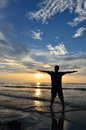 Silhouette of man raising his hands or open arms when sun rising up Stock Image