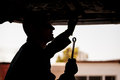 Silhouette of a mechanic at work young holding wrench under suspended car an auto shop Stock Photography