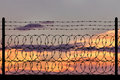 Silhouette of a metal fence with barbed wire