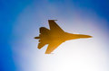 Silhouette of a military fighter sun lights blue sky. Royalty Free Stock Photo
