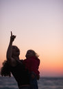 Silhouette of mother with baby in dusk pointing up Royalty Free Stock Photo