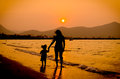 Silhouette of mother and baby walking on sunset family concept Royalty Free Stock Photo