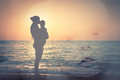 Silhouette of mother and child on the beach and a child s face double exposure Stock Photos