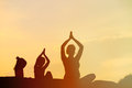 Silhouette of mother and kids doing yoga at sunset Royalty Free Stock Photo