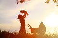 Silhouette of mother with little baby at sunset, happy family Royalty Free Stock Photo