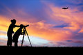 Silhouette of mother and son using camera shooting airplane Royalty Free Stock Photo
