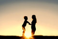 Silhouette of Mother and Young Child Holding Hands at Sunset Royalty Free Stock Photo
