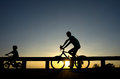 Silhouette motion cyclist bicycles against sunset Royalty Free Stock Photo