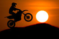 Silhouette of motorbike rider jump cross slope of mountain with sunset background Royalty Free Stock Photography